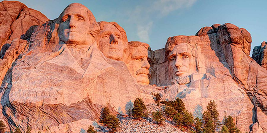 Mount Rushmore National Memorial on a clear blue sunny morning during sunrise showing all four presidents faces in HDR.